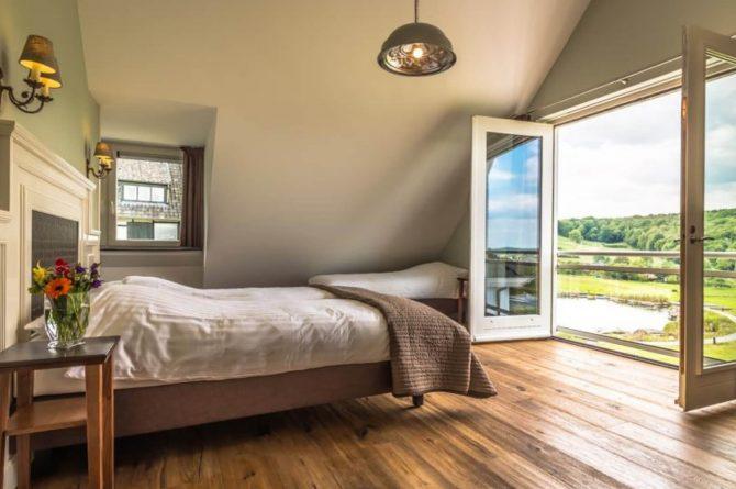 Vakantievilla Schweiberg-Villapparte-De Smockelaer-luxe vakantiehuis voor 18 personen-binnen zwembad-groepsaccommodatie-Zuid Limburg-slaapkamer met uitzicht over de heuvels